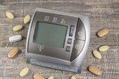 Digital sphygmomanometer blood pressure monitor on background of wooden table. Tonometer Stock Photos