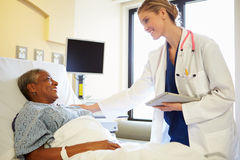 With Digital Tablet与妇女的Talks医生在医院病床上 免版税图库摄影