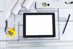Digital tablet with architects tools on blueprint. Closeup of digital tablet with architects tools on blueprint royalty free stock photos