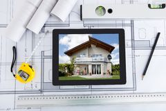 Digital tablet with architects tools over blueprin. House displayed on digital tablet screen with architects tools over blueprint stock photos