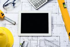 Digital tablet with architectural blueprints rolls and tools. Stock Images