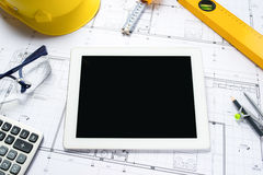 Digital tablet with architectural blueprints rolls and tools Royalty Free Stock Photography