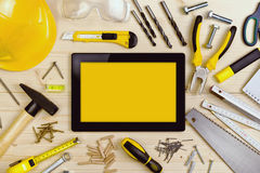 Digital Tablet and Assorted Carpentry Tools  on Workshop Table Royalty Free Stock Photos