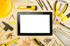 Digital Tablet and Assorted Carpentry Tools  on Workshop Table Royalty Free Stock Photography