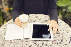 Digital tablet, blank diary and cup of coffee outdoor Stock Images