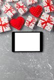 Digital tablet blank screen with gift box and hearts decor on gray cement table. Top view. Valentines Day concept background.  stock image