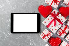 Digital tablet blank screen with gift box and hearts decor on gray cement table. Top view. Valentines Day concept background.  royalty free stock photo