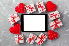 Digital tablet blank screen with gift box and hearts decor on gray cement table. Top view. Valentines Day concept background.  royalty free stock image