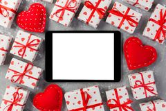 Digital tablet blank screen with gift box and hearts decor on gray cement table. Top view. Valentines Day concept background.  royalty free stock photography