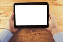 Digital tablet with blank screen in hands on the wooden table Stock Photos