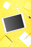 Digital tablet with blank screen and office supplies on yellow tabletop Stock Photo