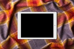 Digital tablet with blank screen on warm coverlet. Spending cold winter at home with modern gadget. Contemporary portable touch pa Royalty Free Stock Photography