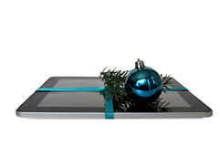 Digital tablet with blue ribbon, Christmas ball and fir branch isolated on white Royalty Free Stock Image