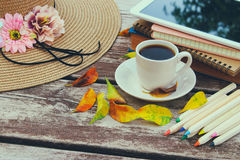 Digital tablet, books, colorfull pencils and cup of coffee on old wooden table outdoor in the park Royalty Free Stock Images
