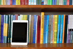 Digital tablet on the books shelves Royalty Free Stock Images