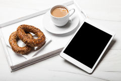 Digital tablet, breakfast and cup of coffee on old wooden desk. Stock Photos