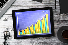Digital tablet with business graph on a wooden table Stock Images