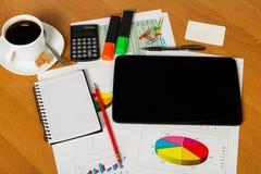 Digital tablet, calculator, coffee, notebook, office supplies on desktop background. Stock Photos