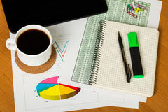 Digital tablet, coffee cup and notebook with pen on desktop. Royalty Free Stock Image