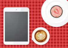 Digital Tablet With Coffee and Cupcake. A digital tablet with blank screen, a coffee with latte art and strawberry cupcake on table. Viewed from top Royalty Free Stock Photos