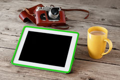 Digital tablet computer with black screen with coffee and vintage camera on wooden background closeup. Copy space. Free space for text. Top view Royalty Free Stock Image