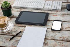 Digital tablet with computer keyboard, smartphone, pot plant, pen, notepad and coffee cup Stock Images