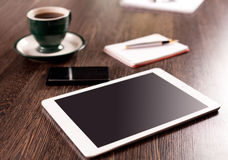 Digital tablet computer with note paper and cup of coffee on old wooden desk Royalty Free Stock Photos