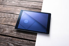 Digital tablet computer on wooden desk. Royalty Free Stock Photos