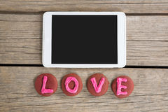 Digital tablet with cookies displaying love message on wooden surface Royalty Free Stock Image
