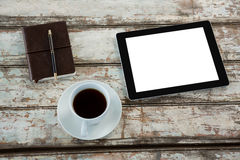 Digital tablet with cup of coffee and organiser. On wooden table Royalty Free Stock Images