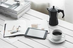 Digital tablet with cup of coffee on a white desk Royalty Free Stock Photos