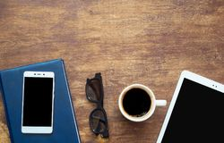 Digital tablet and cup of coffee on wood desk. Smart phone on th stock images