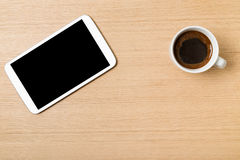 Digital tablet and cup of coffee on wooden table Royalty Free Stock Images