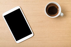 Digital tablet and cup of coffee on wooden table Royalty Free Stock Photography