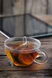 Digital tablet and cup of tea on old wooden table Royalty Free Stock Photo