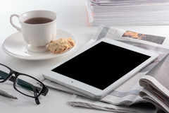 Digital tablet with cup of tea on white background. Royalty Free Stock Photo