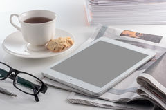 Digital tablet with cup of tea on white table. Stock Images