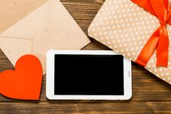 Digital tablet with gifts and hearts on wooden table. View from Royalty Free Stock Photography