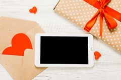 Digital tablet with gifts and hearts on wooden table. View from Royalty Free Stock Image