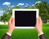 Digital tablet in hands with grass field and trees Stock Image