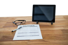 Digital tablet, insurance form, spectacle and pen on desk Royalty Free Stock Photography