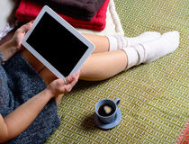 Digital tablet on the legs of a young woman. Digital tablet on the legs with socks of a young woman Royalty Free Stock Photography