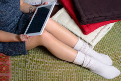 Digital tablet on the legs of a young woman. Whit legging Royalty Free Stock Images