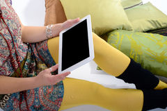 Digital tablet on the legs of a young woman. Digital tablet on the legs with yellow tights of a young woman Royalty Free Stock Image