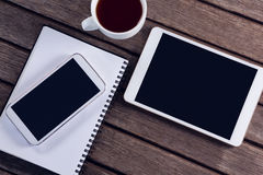 Digital tablet, mobile phone, black coffee and diary on wooden table Royalty Free Stock Photos