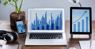 Digital tablet, mobile phone and laptop showing graph at desk. In office Royalty Free Stock Images