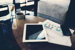 Digital tablet and mobile phone lying on a glass table near paper documents in office interior Royalty Free Stock Photography