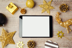 Digital tablet mock up template with Christmas decorations on wooden background. View form above Royalty Free Stock Photos
