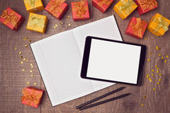 Digital tablet mock up template with gift boxes and notebook on wooden desk. View from above Royalty Free Stock Photography