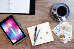Digital tablet, note paper, cup of coffee and money on ol Royalty Free Stock Photos